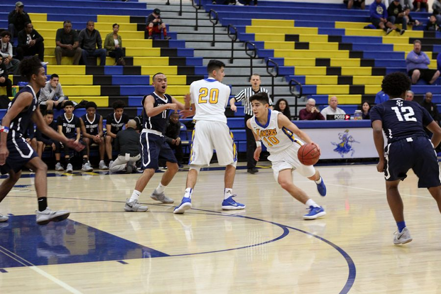 Vincent Rodriguez dribbles the ball while Jimmy Rodriguez blocks the defense.