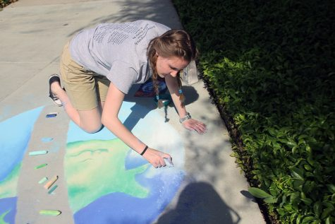 Senior Gillian Jones fills in the clouds to finish up her artwork.