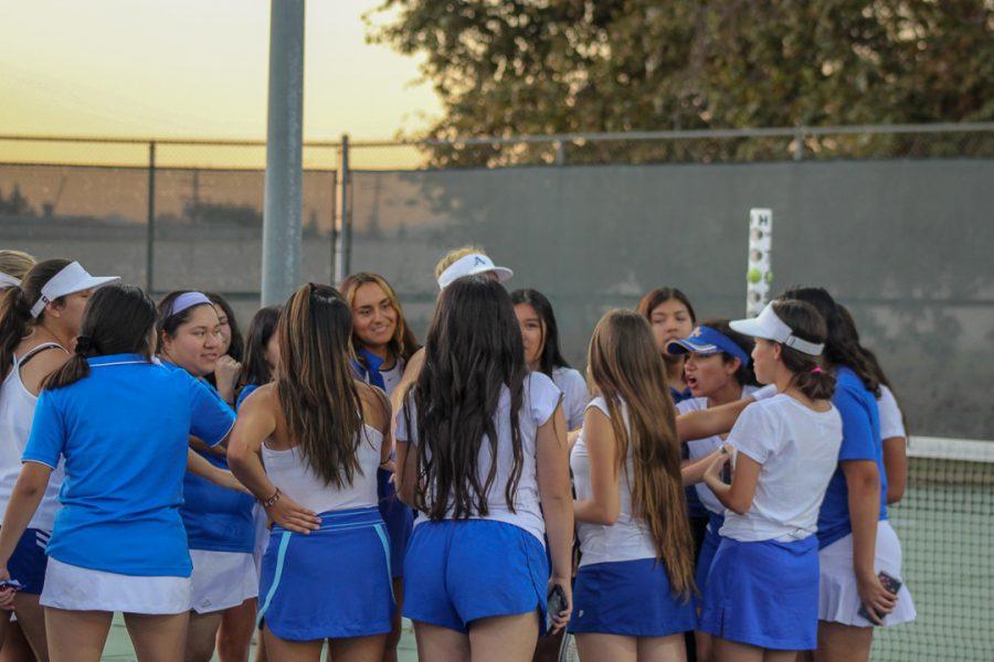 The tennis team huddles up after a tough match.