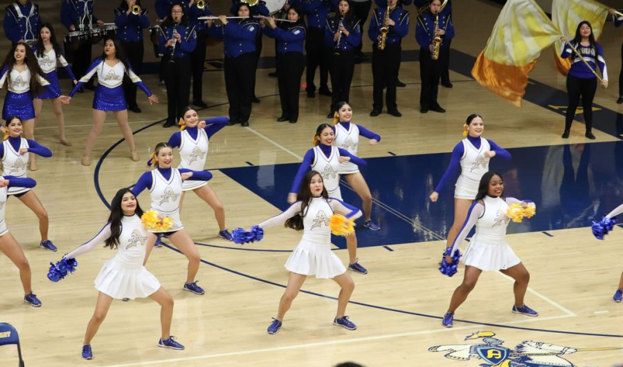 The cheer team is showing some dance moves.