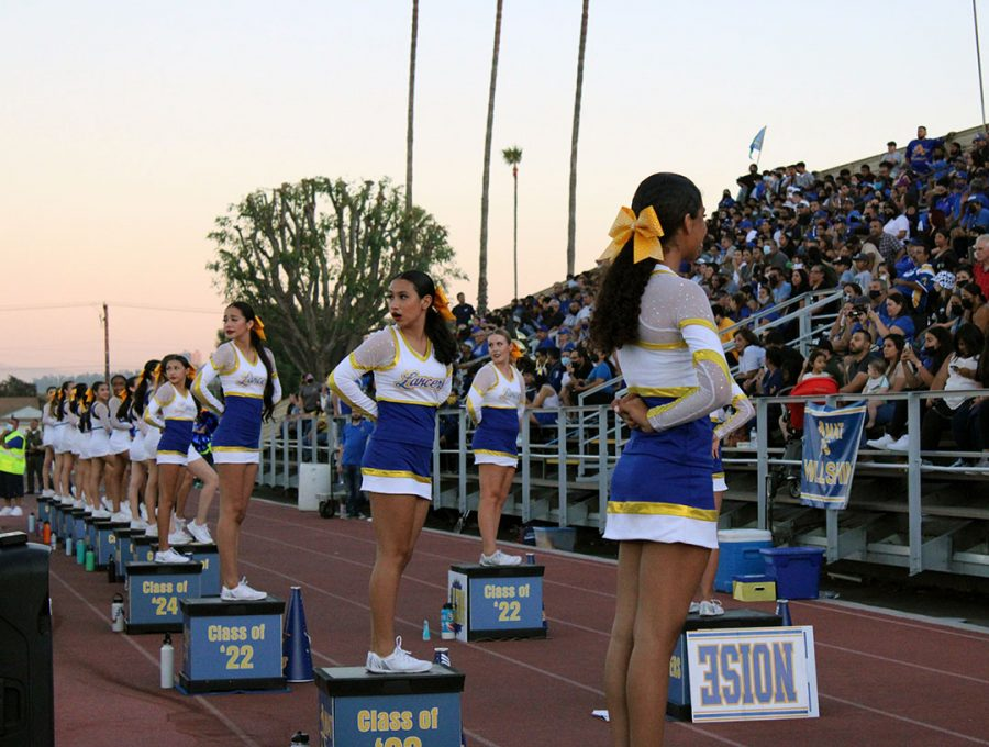 The cheerleaders turning to watch an exciting play on the field.